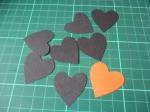 Cut out seven black hearts and one red heart